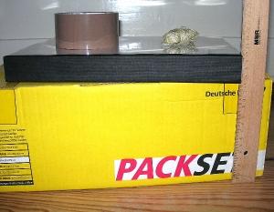 Gelbes Packset mit 3,5 cm dicker Doktorarbeit daraufliegend