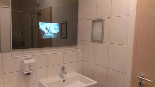 Ein Waschbecken, darüber ein Spiegel auf den Sky-TV projiziert wird