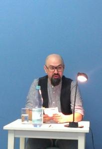 Der Autor vor einer blauen Wand, das Buch in der Hand, vor sich ein Tisch mit Leselampe und Wasserglas