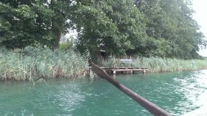 Im Vordergrund ein Ruder überm Wasser, im Hintergrund eine Bank am Seeufer