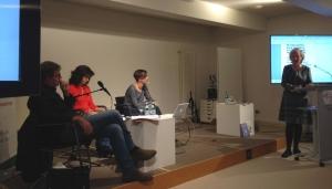 Auf einer Bühne zwischen zwei Großbildschirmen sitzen drei Menschen, die Moderatorin steht am Stehpult davor.
