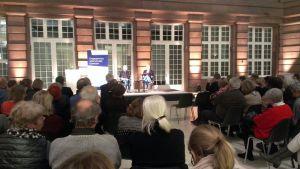 Blick aus dem Publikum auf die Bühne mit Autor und Moderator