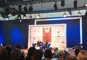 Blaues Sofa mit Autor und Moderatorin, dahinter eine Projektion des Buchcovers