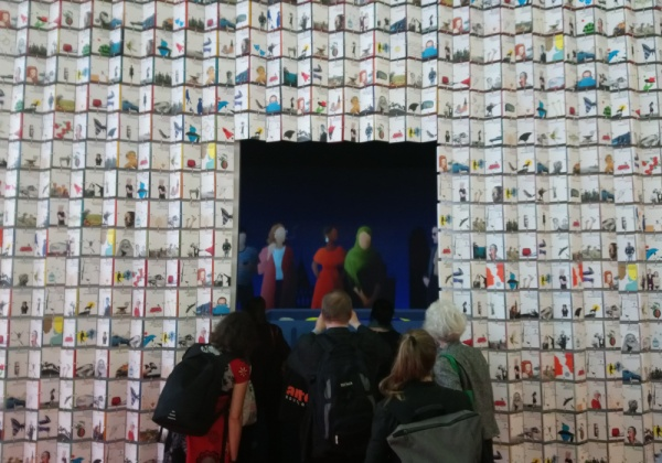 Wand aus aneinandergehefteten Büchern mit einer Tür, die den Blick auf einen großen Screen im Inneren des Kubus freigibt