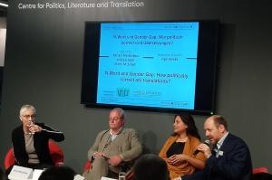 Vier Menschen auf dem Podium in roten Sesseln, dahinter ein Screen mit dem Titel der Veranstaltung